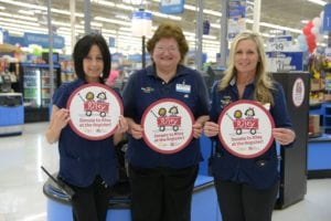 Walmart associates holding Donate to Riley at the Register signs